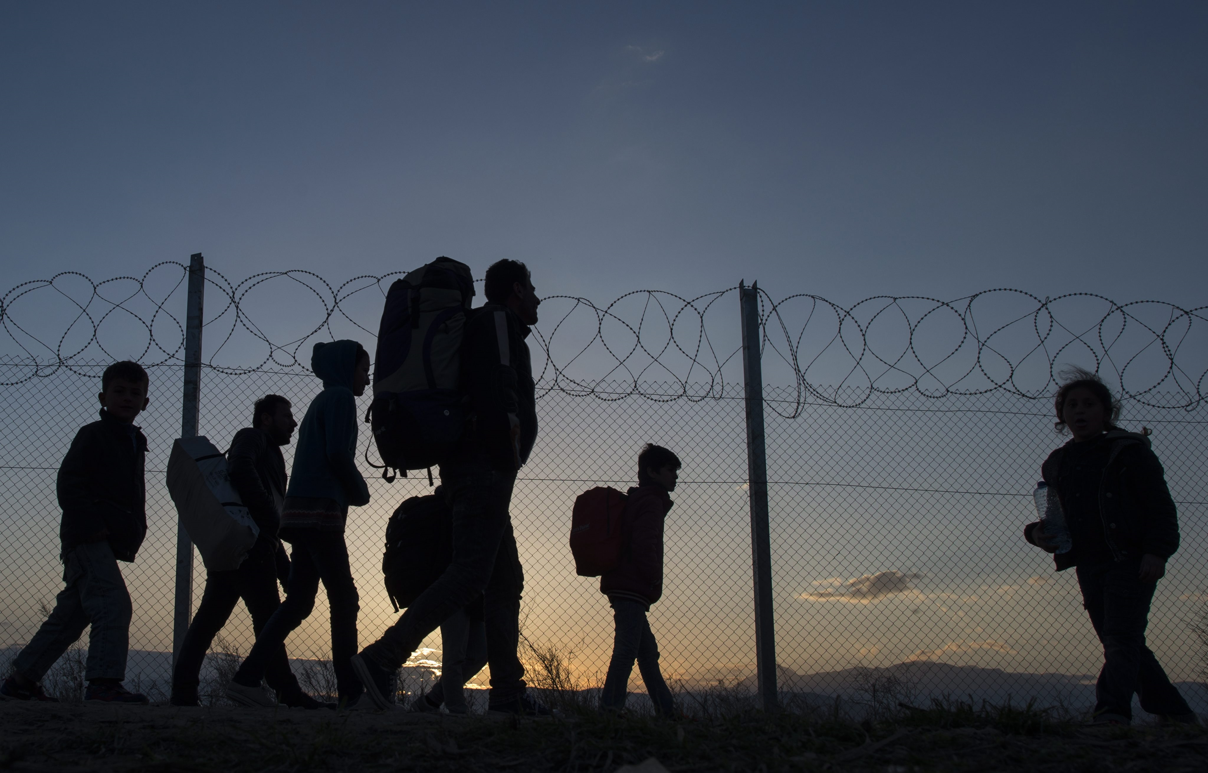 Migrants walk to transit camp after entering Macedonia